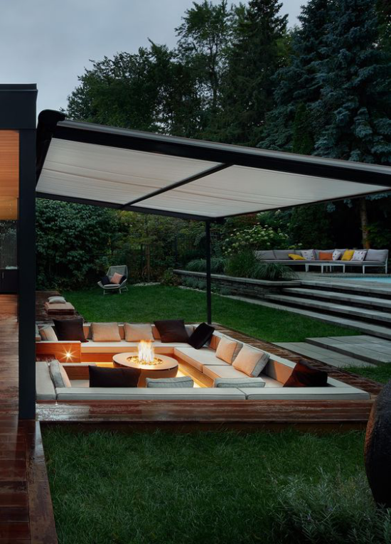 versunkener Sitzbereich im Freien moderne Lounge-Zone unter Segel Feuerstelle in der Mitte sehr stilvoll und einladend