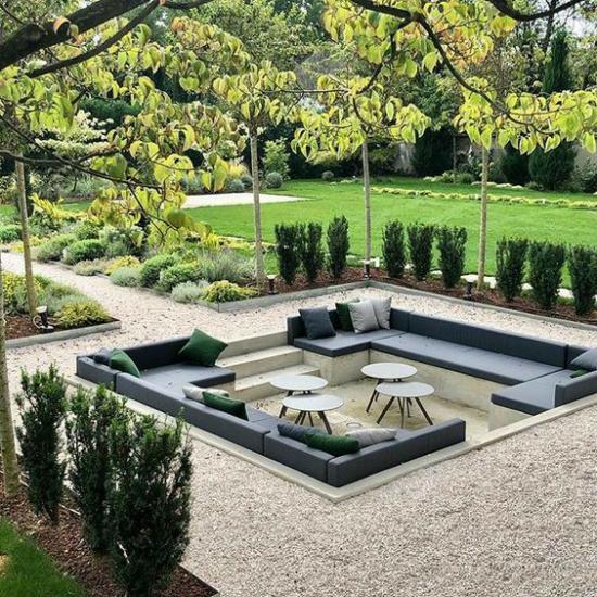 versunkener Sitzbereich im Freien stilvolle Gestaltung viereckig gepolsterte Sitzbänke Kieselstein grüne Pflanzen rundherum