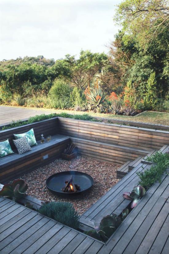 versunkener Sitzbereich im Freien viereckige Fläche Naturmaterialien Holz Kieselsteine viele Bäume
