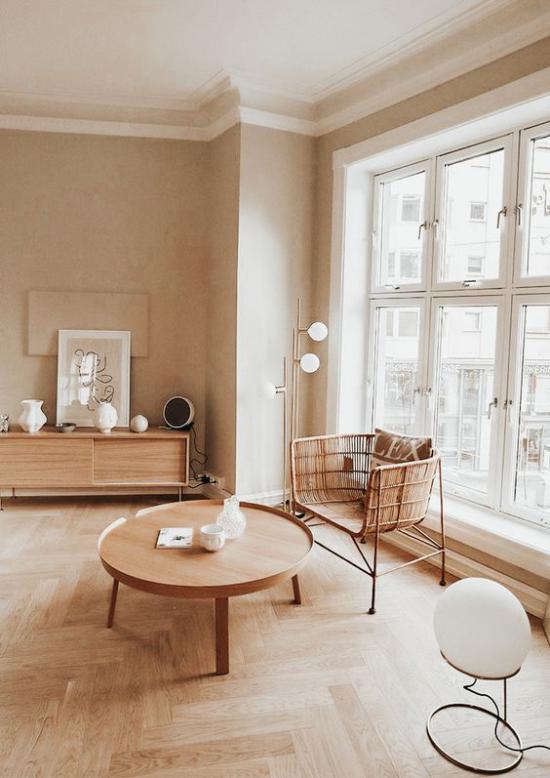 zeitlose Farben einfach eingerichtetes Wohnzimmer Weiß Beige und viel Holz Parkettboden geflochtener Sessel runder niedriger Holztisch