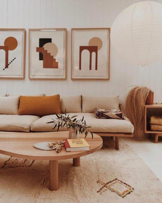 zeitlose Farben gemütliches Wohnzimmer in warmen Erdnuancen weiß beige gebrannte Siena Sofa Teppich Wanddekoration runder niedriger Holztisch