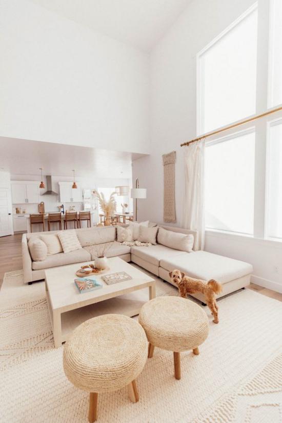 zeitlose Farben im Wohnzimmer Ecksofa in Beige Hocker in Hellbraun heller Teppich Küche im Hintergrund Hund
