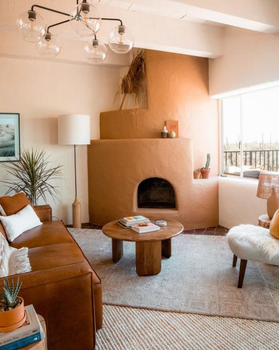 zeitlose Farben warmes einladendes Wohnzimmer Blickfang Kaminofen in gebrannter Siena Ledersofa links runder Holztisch
