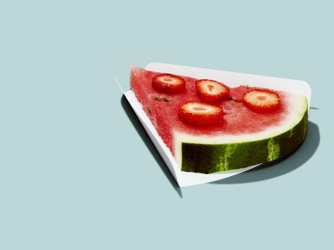 Diät-Regeln gesund abnehmen ein Stück Wassermelone garniert mit Erdbeeren kaum Kalorien