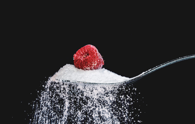 Diätfallen frisches Obst essen ohne Zucker eine Himbeere auf einem Haufen Zucker lecker aber ungesund