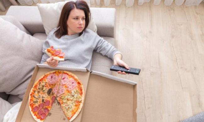 Diätfallen junge Frau liegt auf der Couch vor dem Fernseher isst Pizza schlechte Gewohnheit
