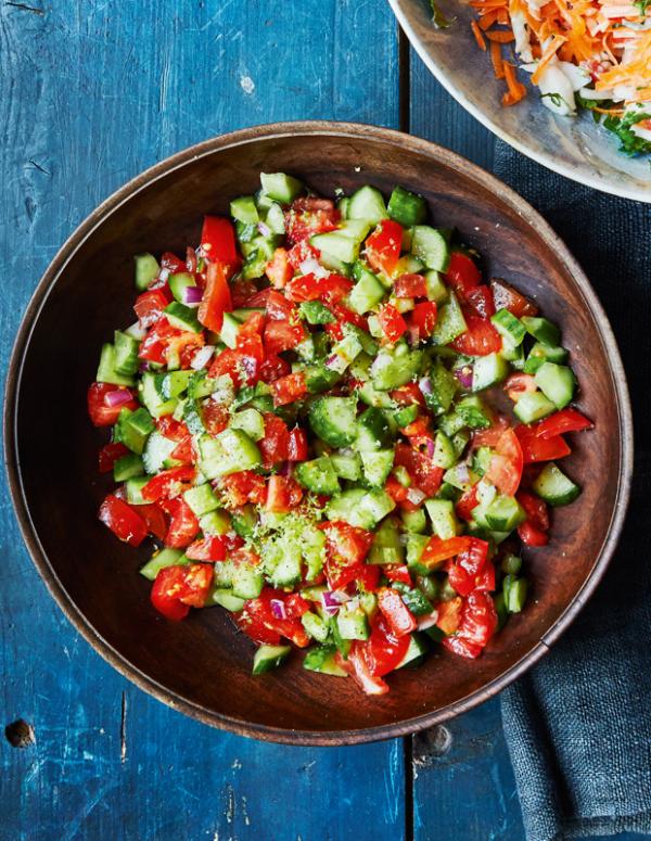 Frische Sommersalate rote Tomaten Gurken Zwiebeln klein geschnitten