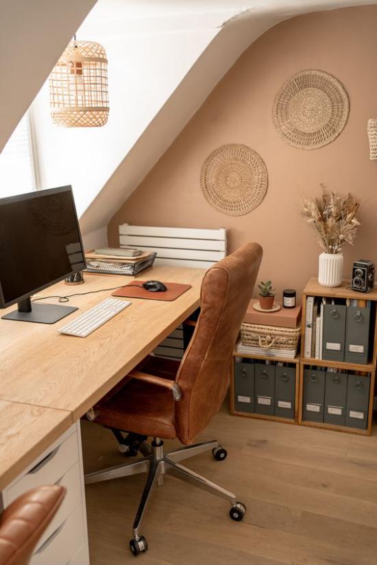 Heimbüro auf dem Dachboden beigefarbene Akzentwand helles Holz Sessel mit Samt überzogen handgemachte Wanddekoration