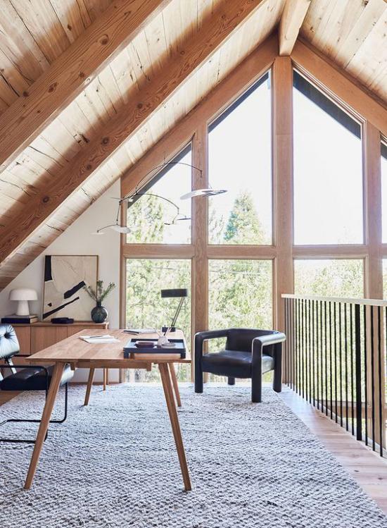Heimbüro auf dem Dachboden hervorragende Idee unter der Dachschräge helles Holz schicke Möbel viel Tageslicht Schreibtisch Lampe Ledersessel