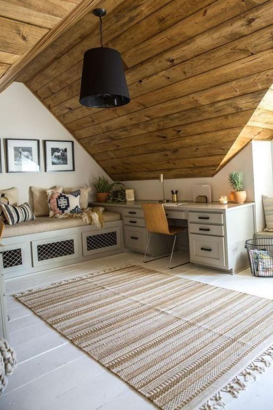 Heimbüro auf dem Dachboden sehr gemütliches und romantisches Ambiente viel Holz weiche Textilien Kissen auf der Sitzbank Teppich