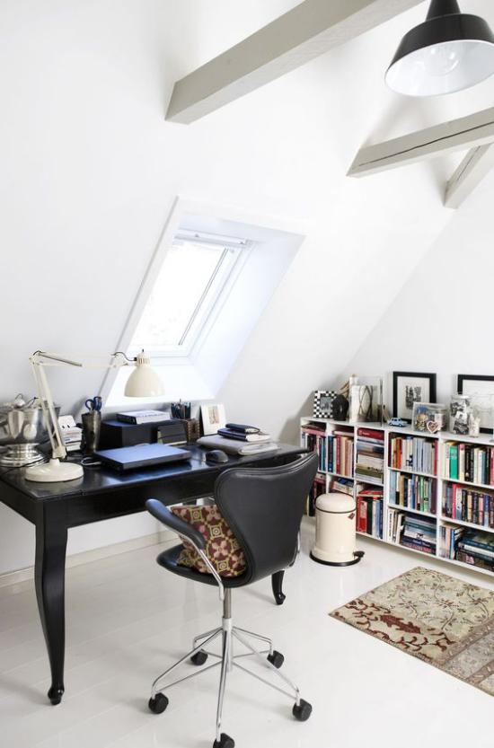 Heimbüro auf dem Dachboden weißes Ambiente schwarze Büromöbel niedriges Bücherregal an der Wand