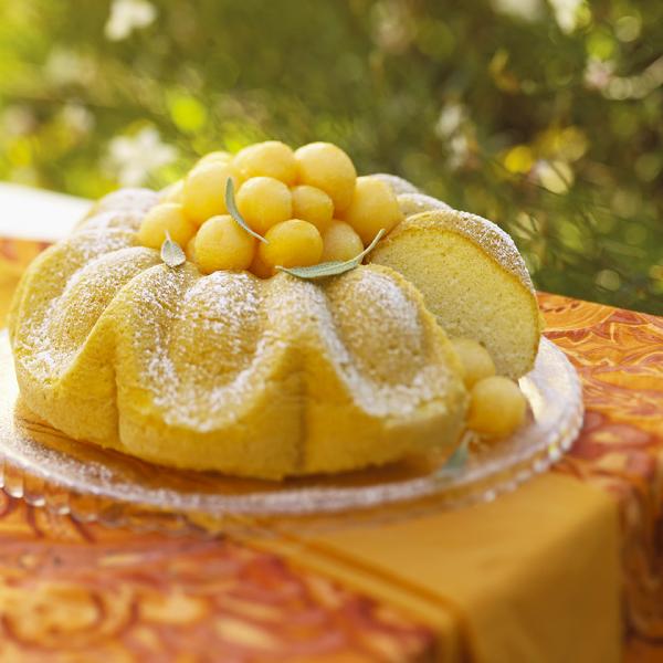 Melonen-Desserts Zitronenkuchen mit Melonenkugeln und Puderzucker garnieren