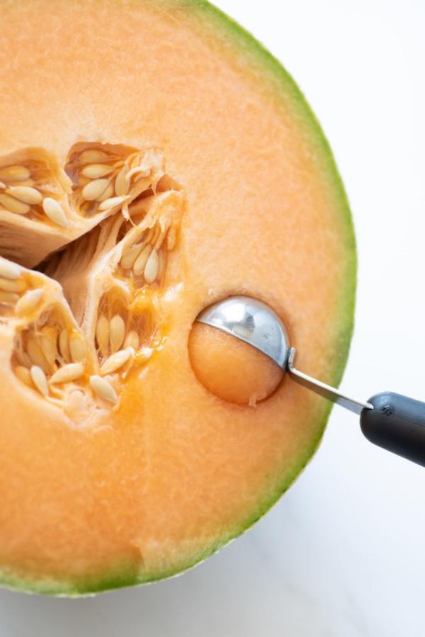 Melonen-Desserts Halbierte Honigmelone mit einem Kugelausstecher zu Kugeln formen
