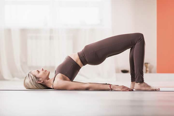 Attractive blonde woman in sports beige leggings and tank top, p