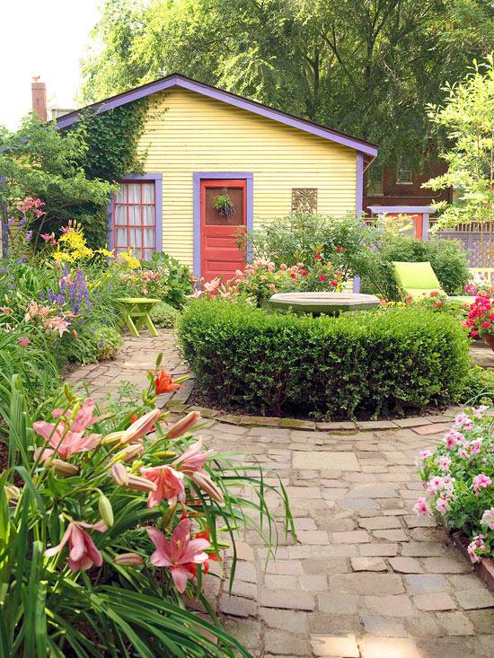 mehr Farbe in den Garten bringen rosa Lilien und Pelargonien am Rande des Blumenbeetes schöner Blick in einen Bauerngarten