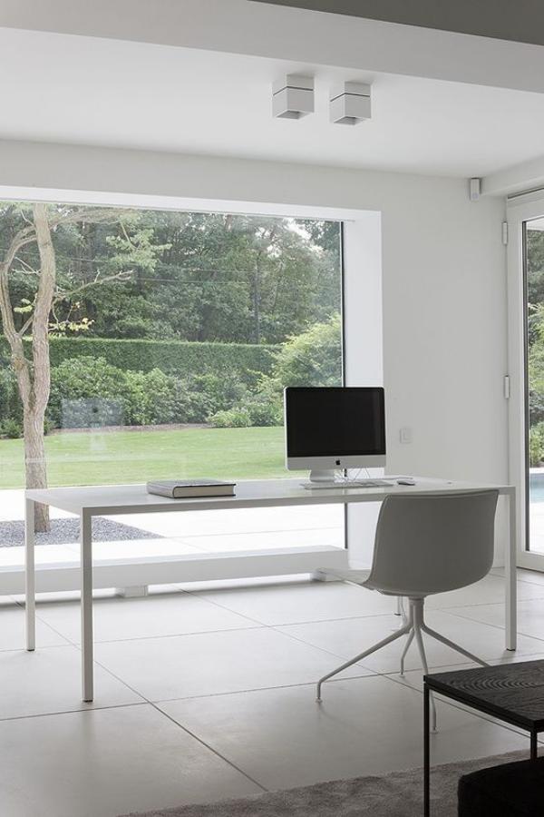 minimalistisches Home-Office elegante Büroeinrichtung helle Farben große Glastür Blick zum Garten