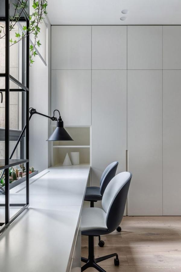 minimalistisches Home-Office viel Tageslicht langer Tisch vor dem Fenster Grau dominiert Schreibtischlampe