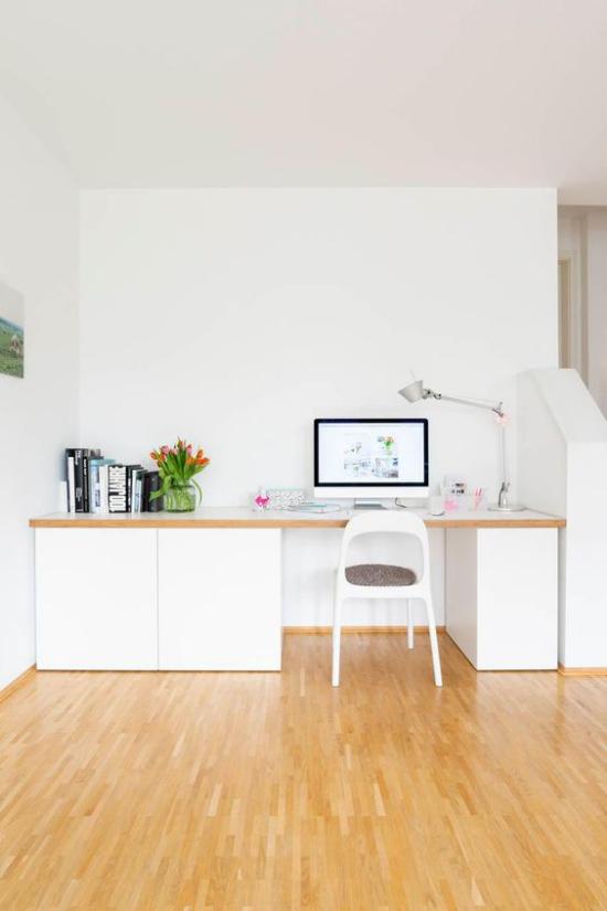 zeitgenössisches Home Office Holzboden weiße Büromöbel sauberes Ambiente Bücher daneben Vase mit Tulpen