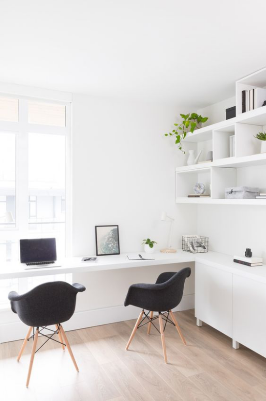 zeitgenössisches Home Office ansprechendes Ambiente Weiß dominiert Fenster Licht zwei schwarze Sessel als Kontrast
