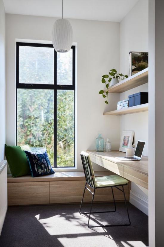 zeitgenössisches Home Office einfach aber gemütlich eingerichtet Sitzbank weiße Kissen am Fenster Schreibtisch offenes Regal helles Holz