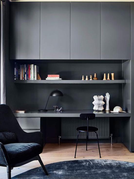 zeitgenössisches Home Office grau dominiert etwas düster wirkt Schreibtisch Oberschränke Stauoptionen dunkler Ledersessel schwarzer Stuhl Teppich