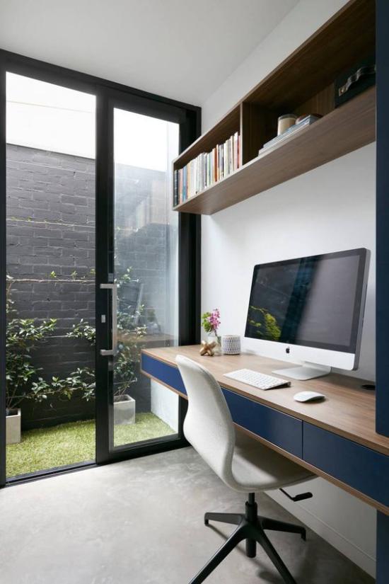 zeitgenössisches Home Office große Glastür Blick zum Innenhof langer Schreibtisch PC weißer Sessel Regal