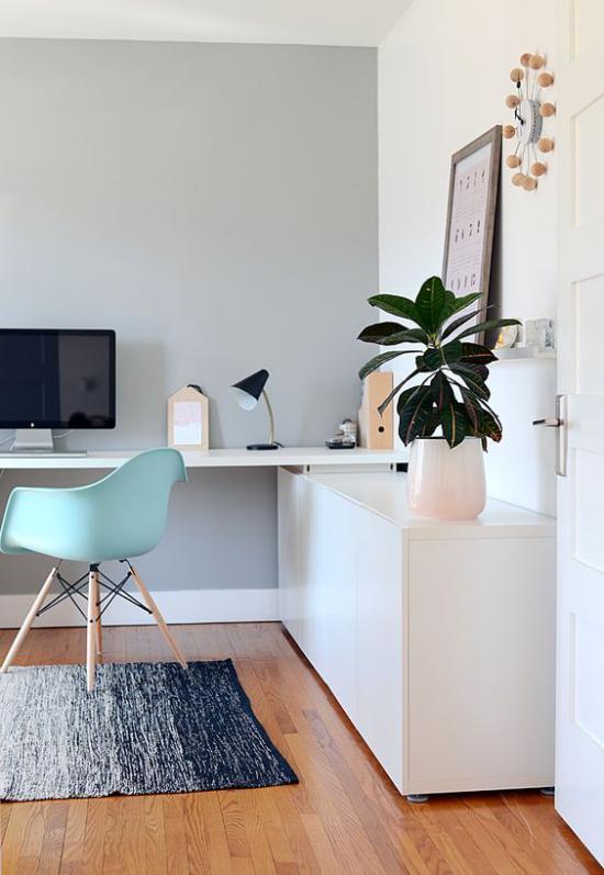 zeitgenössisches Home Office helle Farben Laptop hellgrüner Stuhl schöner Blumentopf Grünpflanze als Blickfang