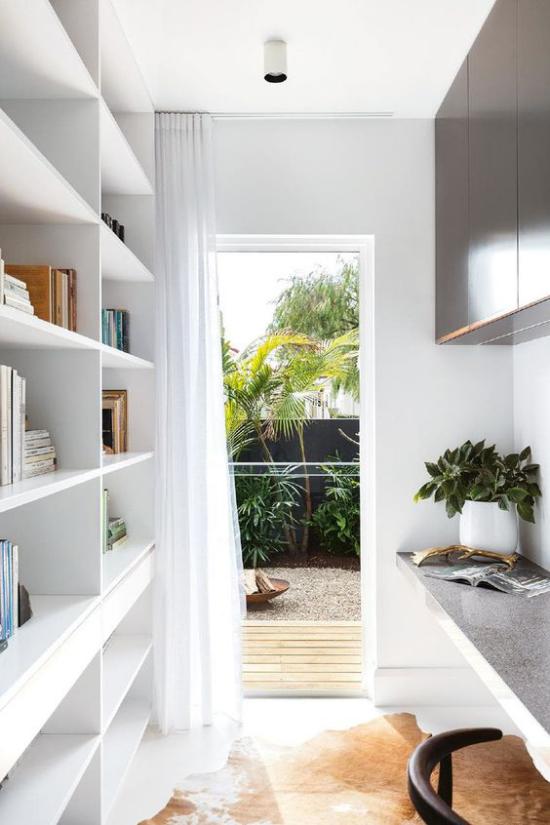 zeitgenössisches Home Office weißes Regal links Schreibtisch weißer Topf Grünpflanze als Blickfang