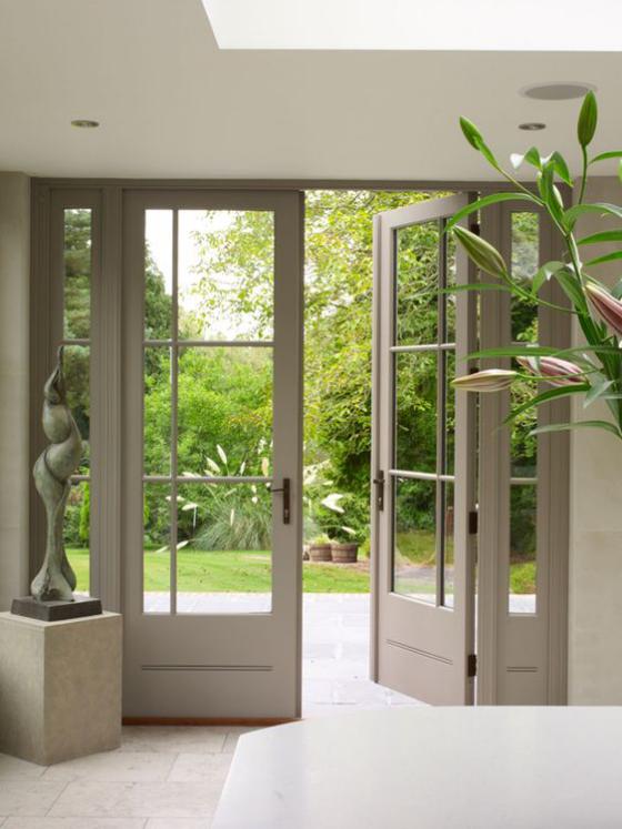 französische Fenstertüren ein Flügel geöffnet Übergang zum gepflegten und meisterhaft gestalteten Garten Statue Grünpflanze im Inneren