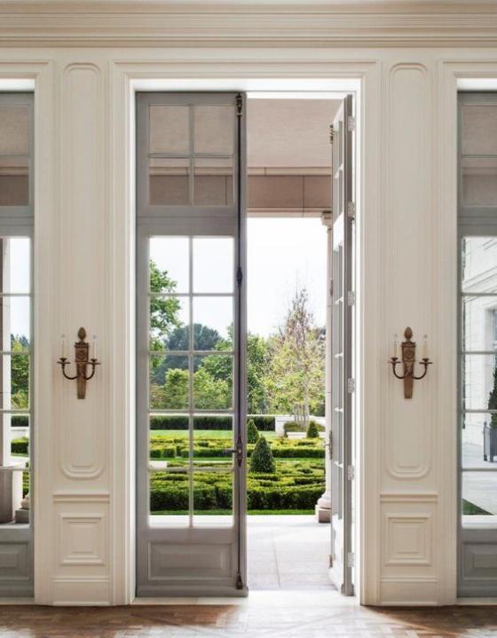 französische Fenstertüren elegantes Raumdesign im klassischen Stil Kerzenständer beiderseits Übergang zum Garten sehr gut gestaltet und gepflegt