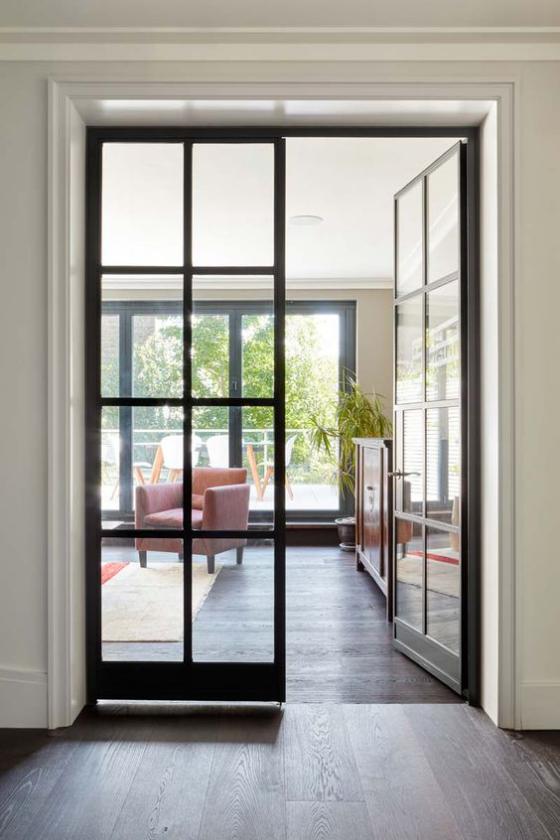 französische Fenstertüren zwei Flügel schwarzer Rahmen Übergang zum elegant gestalteten Wohnzimmer