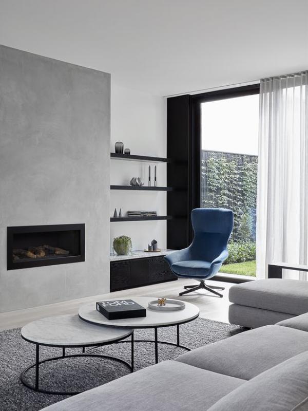 modernes Wohnzimmer Grau als Grundfarbe kleine schwarze Akzente ein Designklassiker blauer Sessel als Blickfang