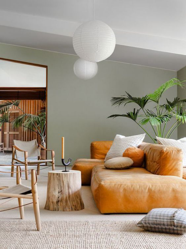 modernes Wohnzimmer Weiß Hellgrau Sand Ledersofa Naturmaterialien Baumstamm Hängeleuchten Grünpflanze im Topf