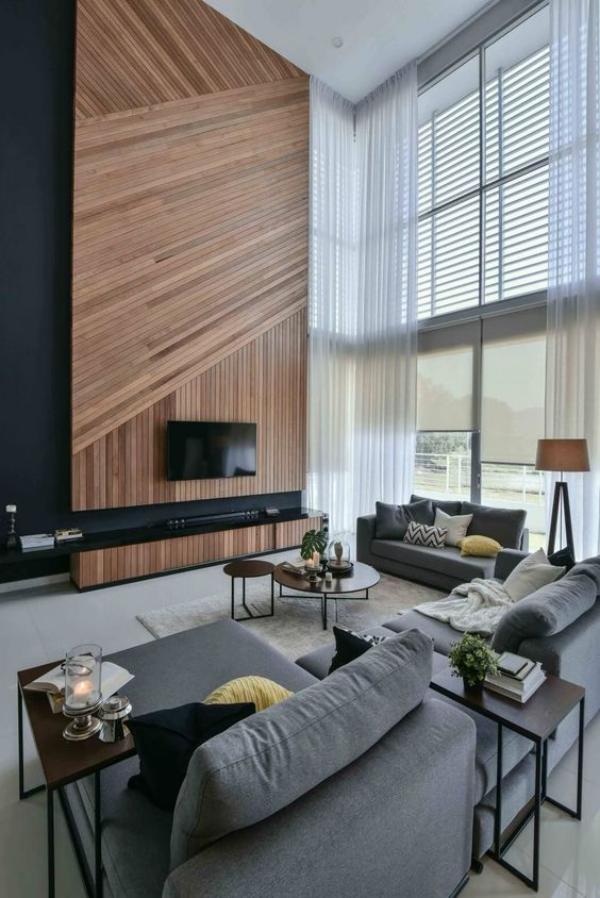 modernes Wohnzimmer auf zwei Ebenen Holzwand als Blickfang graue Sitzmöbel Kissen Tische Kerzen einladend und gemütlich wirken