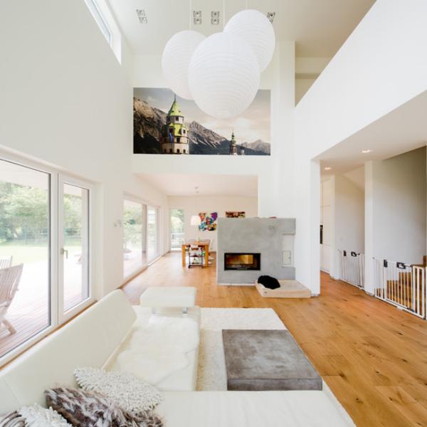 modernes Wohnzimmer auf zwei Ebenen schicke Raumgestaltung in Weiß Hängeleuchten Wandbild helles Holz auf dem Boden Betonwand mit Kamin