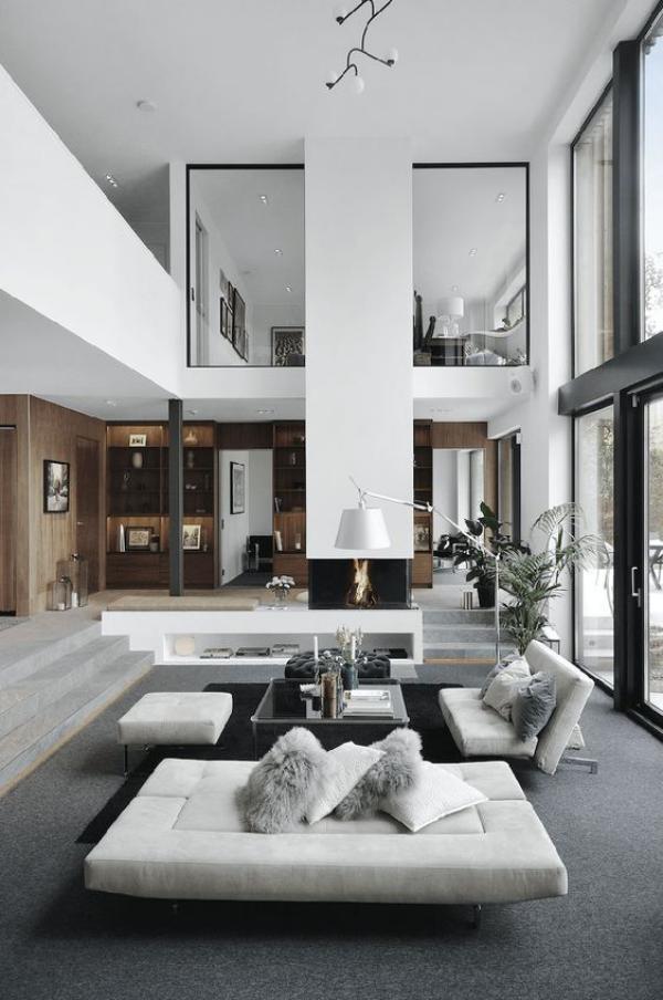 modernes Wohnzimmer auf zwei Ebenen schickes Interieur weiße Möbel grauer Bodenbelag Bogenlampe Wurfkissen auf den Sofas