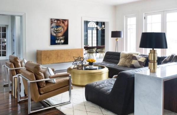 modernes Wohnzimmer eklektisches Raumdesign Ledersessel schwarzes Ledersofa goldglänzender runder Tisch in der Mitte Wandbilder zu viele Farben