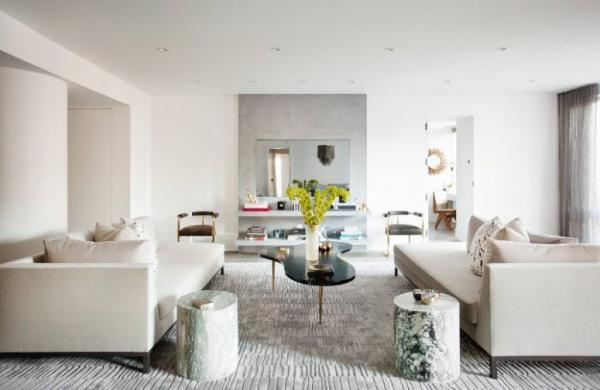 modernes Wohnzimmer geometrische Formen helle Farben zwei Sofas Teppich kleiner schwarzer Kaffeetisch zwei Baumstammhocker