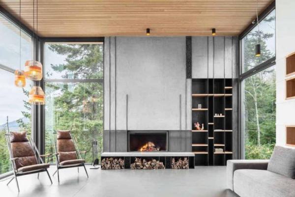 modernes Wohnzimmer sauberes Ambiente wenige Möbel Kamin Brennholz zwei Sessel deckenhohe Fenster Blick auf die Natur