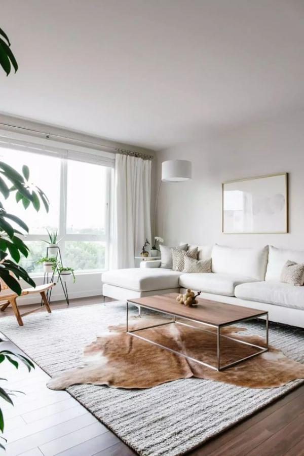 modernes Wohnzimmer schickes Ambiente großes Fenster viel Tageslicht weißes Sofa Kaffeetisch in der Mitte braunes Fell darunter