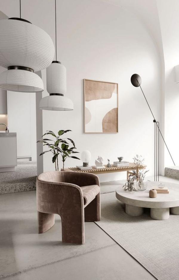 modernes Wohnzimmer stilvolle Raumdeko sauberes aufgeräumtes Ambiente wenig Möbel Sessel als Blickfang Wandbild Vasen Topfpflanzen