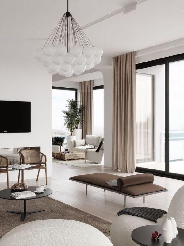 modernes Wohnzimmer weiß grau taupe interessante Möbelanordnung viel Luft im Raum hellbraune Fenstergardinen schicker Kronleuchter grüne Topfpflanze im Hintergrund
