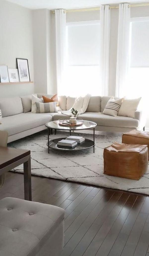 modernes Wohnzimmer weißes Ecksofa weißer Teppich zwei Retro-Hocker aus Leder in Ocker Farbe Hingucker