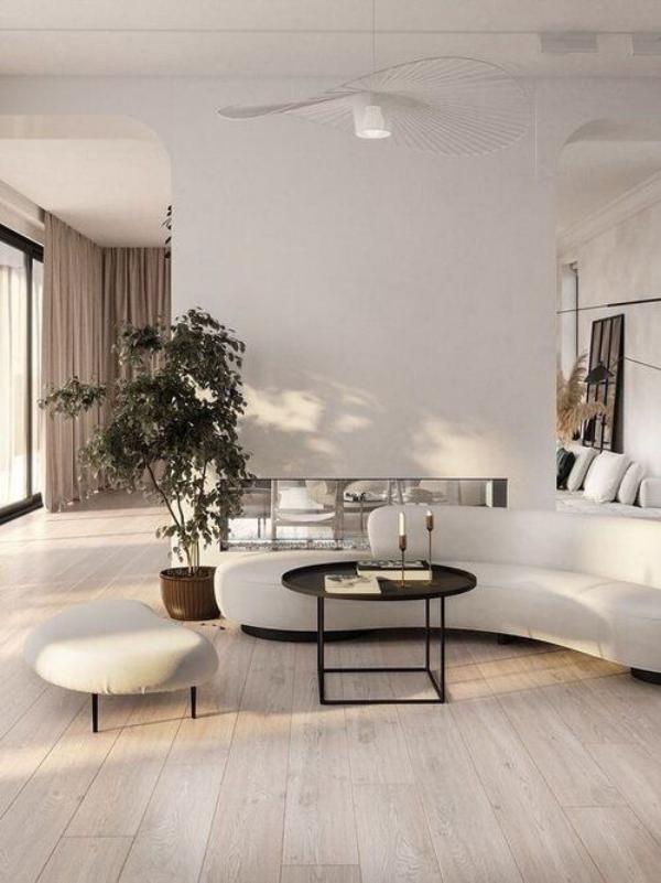 modernes Wohnzimmer weißes Interieur gerundete Möbel Sofa Hocker kleiner Kaffeetisch Trennwand in Weiß grüne Topfpflanze