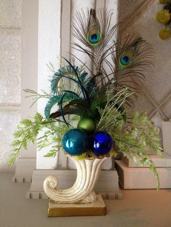 winterdeko mit pfauenfedern und weihnachtsschmuck