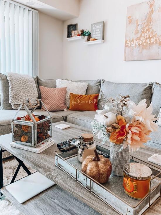Herbstdeko auf dem Kaffeetisch Grau mit Orange kombinieren Tablett Kürbis Vase mit Blumen Laterne mit Zapfen gefüllt Holztisch