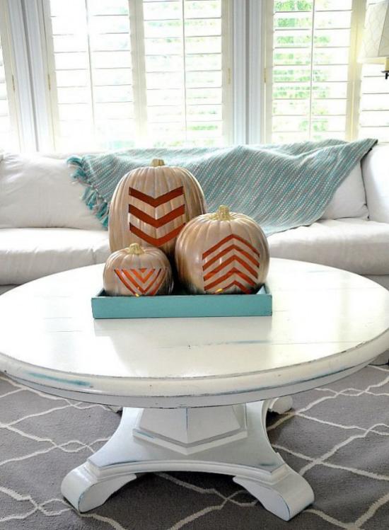 Herbstdeko auf dem Kaffeetisch drei Kürbisse geschnitzt graviert schickes Arrangement auf einem weißen runden Tisch blaues Tablett hellblaue Wurfdecke auf dem weißen Sofa