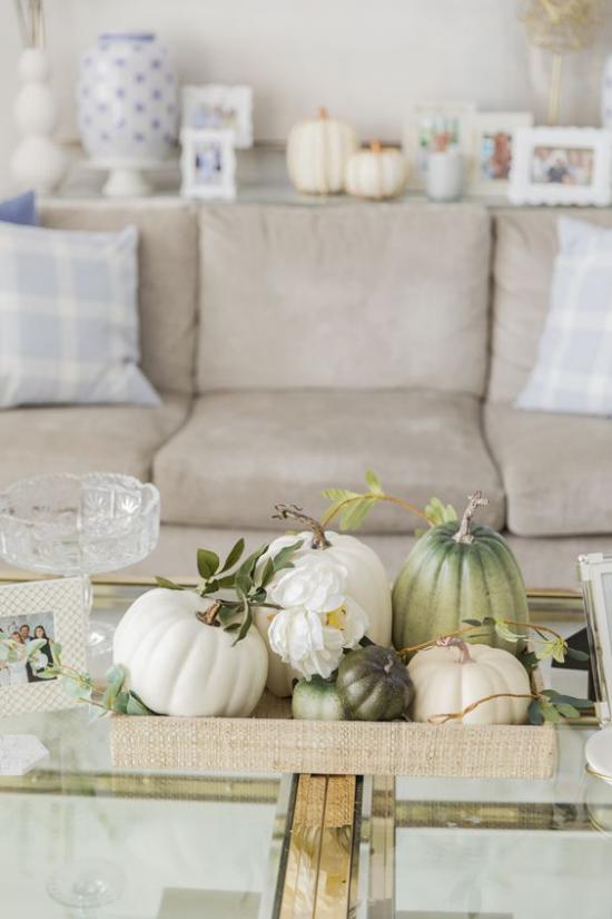 Herbstdeko auf dem Kaffeetisch klassisches gemütliches Wohnzimmer Möbel in hellen Farben Tisch aus Glas weiße Kürbisse auf Tablett etwas Grünzeug
