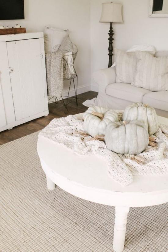 Herbstdeko auf dem Kaffeetisch rustikales Interieur ganz in Weiß weiße Kürbisse weiße Strickdecke auf einem weißen runden Holztisch