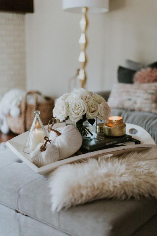 Herbstdeko auf dem Kaffeetisch weiße Kürbisse weiße Rosen Kerzen im weißen Gefäß Pelz